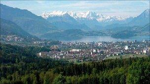 Abird's eye view of Zug with snowcapped mountains, forests and a lake.