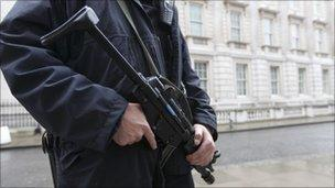 An armed police officer stands on duty in Downing Street, London
