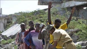 A Somali government soldier frisks a resident in the streets in southern Mogadishu