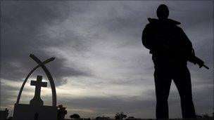 A soldier stands guard at the funeral of victims of a shooting in Ciudad Juarez