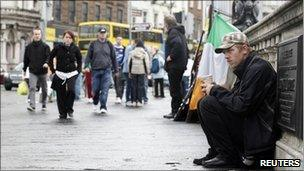 A homeless man sits on O'Connell Bridge in the centre of Dublin