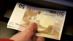 Euro notes being taken from a Berlin cashpoint - file pic