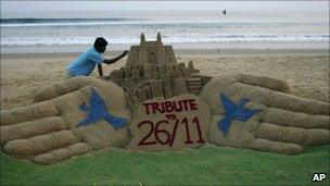 Indian sand artist Sudarshan Pattnaik gives finishing touches to a sand sculpture ahead of the second anniversary of the Nov. 26, 2008