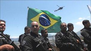 Brazilian police plant a flag in the Complexo do Alemao slum in Rio de Janeiro on Sunday