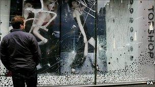 A man inspects damage to the windows of Topshop in Oxford Street