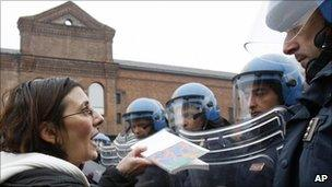 Researchers and students offer books to police officers during a protest in Milan, 22 December 2010