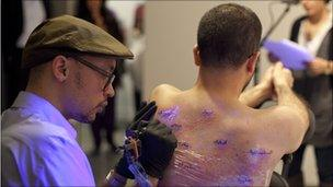 Wafaa Bilal having his back tattooed with a map of Iraq. Photo by Brad Farwell