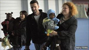 French adoptive families hold newly-adopted children upon arrival in Paris on 22 December 2010