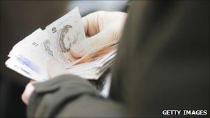 Hands holding a pile of sterling notes (Getty Images)