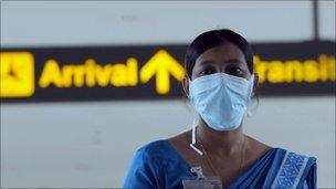 A Sri Lankan health official monitors passengers at the airport in June 2009