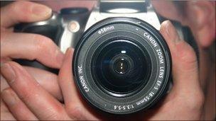 hand holding SLR camera