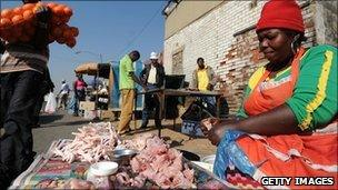 A woman sells chicken by the roadside at Alexandra township, near Johannesburg