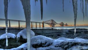 ice frames the Forth Bridge on a frosty day