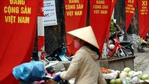 A street vendor walks past banners promoting the party congress in Hanoi on 6 Jan 2011