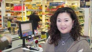 Ms Young A Hong stands in front of the checkout counters at the Korea Foods supermarket