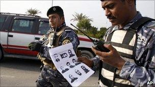 Iraqi policemen holds document showing the escaped detainees