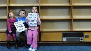 Children with empty library shelves as part of a campaign in Stony Stratford Library, Milton Keynes