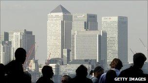 Workers silhouetted in front of the Canary Wharf skyline, London