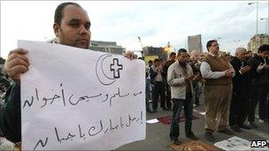 A Copt holds a sign as Muslims pray in Tahrir Square, 31 January