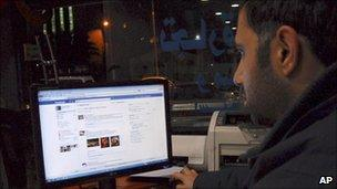 A man uses Facebook in a cafe