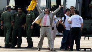 Hostage Armando Acuna raising his arms in triumph in front of the Brazilian helicopter that brought him out of the jungle