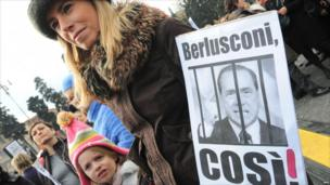A mother holds a placard reading 'Berlusconi, like that!' at Rome's Piazza del Popolo on 13 February 2011