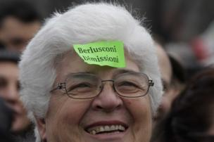 "Woman sports a sticky note against Italian premier Silvio Berlusconi reading ""Berlusconi resign"" during a protest in Milan"