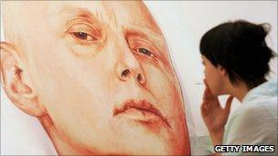 A woman looks at a painting of Alexander Litvinenko