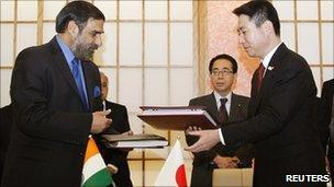 India's Trade Minister Anand Sharma and Japan's Foreign Minister Seiji Maehara exchange documents.