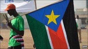 A man holds a SPLM flag in Juba - 30 January 2011