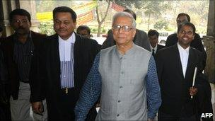 Nobel prize winner and microfinance pioneer Muhammad Yunus (in grey vest) appears for a court hearing in Dhaka