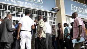 People wait in line on 16 February 2011 in front of a branch of the pan-African bank Ecobank in Abidjan