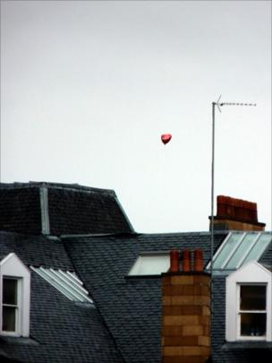 Heart-shaped balloon floating over rooftops