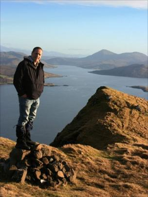 Man standing on the summit of Ben Tianavaig