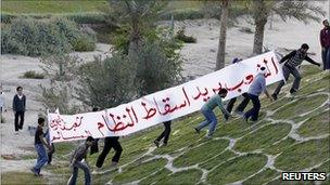 Protesters carry a banner as they walk at the Pearl Roundabout in the Bahraini capital Manama, 15 February 2011