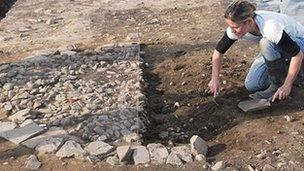 Worker excavating the site of a bread oven