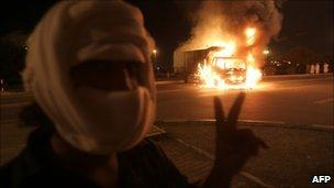 A masked Omani protester flashes victory signs in Muscta, 27 Feb
