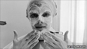 A woman applying face cream with her hands
