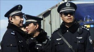 Chinese police officers stand on duty near the Xidan shopping district, one of two sites designated on an Internet call for protest, in Beijing on Sunday