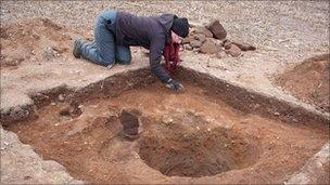 Archaeologists excavate the ground around the stone