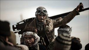 A Libyan rebel fighter stands by a machine gun at a check point in Brega