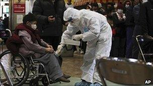 Woman in wheelchair undergoing radiation scan