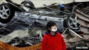 A boy looks on in front of an overturned car among debris in Otsuchi, Iwate prefecture