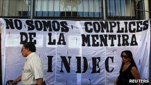 "People walk by a banner that reads ""We are not accomplices of the lie"" placed by union workers outside Argentina's INDEC statistics agency in Buenos Aires, 2March, 2011"