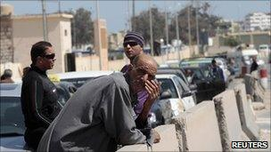 Libyans wait with their cars near a petrol station in Tripoli, 27 March 2011
