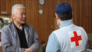 Ken Minato (L), a fisherman in the community of Yamada, Iwate prefecture, talks with a volunteer from the Japanese Red Cross Society. Minato now lives in an evacuation centre with more than 260 of his neighbours after their homes were destroyed by the tsunami. Photo: Owaki Mutsuhiko / Japanese Red Cross Society