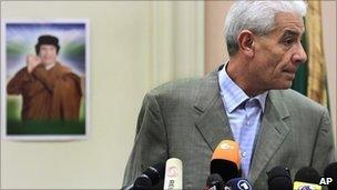 Libya's Foreign Minister Moussa Koussa reads a statement to foreign journalists at a hotel in in Tripoli, in this Friday March 18, 2011