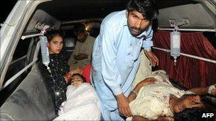 Pakistani blast victims wait for help in an ambulance outside a hospital in Multan on April 3, 2011
