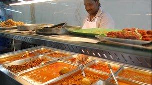 Worker serving food in Malaysian restaurant