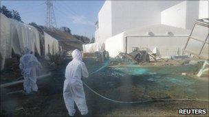 Workers spray adhesive synthetic resin over the ground at the nuclear plant